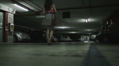 Woman walking alone through car park is followed by suspicious male - stock footage