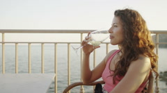 Portrait of beautiful woman drinking wine outdoors as the sun begins to set Stock Footage