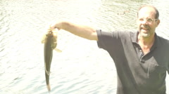 Man holding giant bass fish Stock Footage