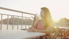 Portrait of beautiful woman drinking wine outdoors as the sun begins to set - stock footage