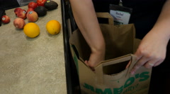 Bagger in a Grocery store bagging fruit. Stock Footage