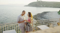 Happy romantic couple drinking wine at outdoor bar or restaurant beside the sea Stock Footage