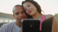 Happy attractive couple with mobile phone, sitting beside the sea at sunset - stock footage