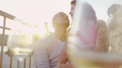 Attractive romantic couple with glasses of wine at beachside bar Stock Footage