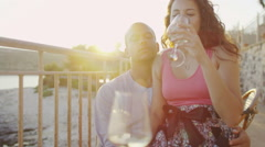 Attractive romantic couple with glasses of wine at beachside bar - stock footage