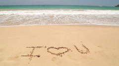 I LOVE U written in the beach sand washed aways by waves. Stock Footage