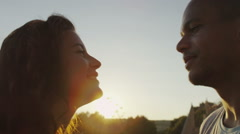 Happy romantic couple outdoors at sunset, make a heart shape with their hands Stock Footage