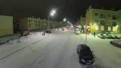 Citizens and cars on illuminated street among identical houses Stock Footage