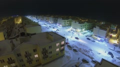 Cars and people on illuminated street among identical houses Stock Footage