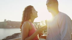 Happy romantic couple drinking wine at outdoor bar or restaurant beside the sea - stock footage