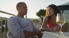 Attractive couple having a conversation at beachside bar at sunset Stock Footage
