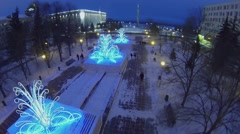 People walk by square with shiny adornments at winter evening. - stock footage