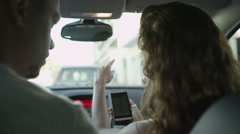 Couple in car driving through the city, using mobile phone as navigation device Stock Footage