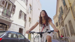 Attractive woman cycling through the city in summertime Stock Footage