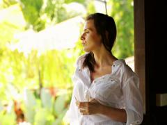 Young, happy woman drinking water by the window of the country house NTSC Stock Footage