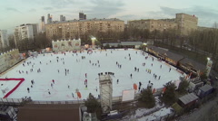 People slide by outdoor skating rink near dwelling houses Stock Footage