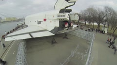 People walk by quay near USSR space shuttle Buran. Aerial view Stock Footage