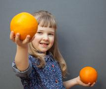 smiling little girl with big orange, grey backgriund - stock photo