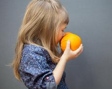 Little girl smelling a ripe orange, grey background Stock Photos