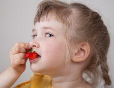 pretty little girl with ripe strawberry - stock photo