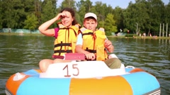 Son and mother floating the river inside electric rubber boat - stock footage