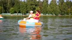 Son and mother floating around inside a rubber boat - stock footage