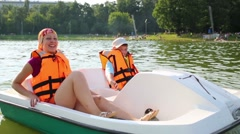 Son and mother in life jackets floating inside a twin hull boat Stock Footage