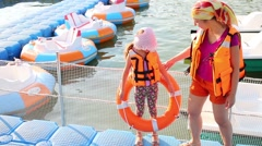 Mother and daughter on the dock with inflatable boats Stock Footage