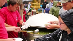 People eat fish broth at Fishermans Day in the Exhibition Center Stock Footage
