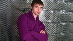 Young male model in purple jacket against mirrored wall Stock Footage