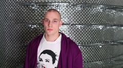 Young man in purple jacket and white T-shirt with picture Stock Footage