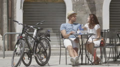 Couple relaxing together at outdoor cafe table in the city  Stock Footage