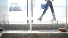 Female legs walked into a glass door with carpet on the floor Stock Footage