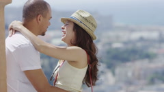 Romantic couple share a kiss with city view in the background Stock Footage