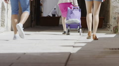 Low angle view of people walking through city street in the summer Stock Footage