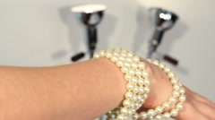 Two female hands with wrapped beautiful pearl beads Stock Footage