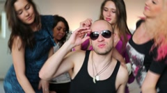 Bald man in shirt with an amulet and beautiful dancing girls Stock Footage