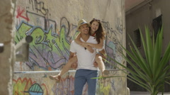 Attractive young couple in European town with graffiti wall Stock Footage