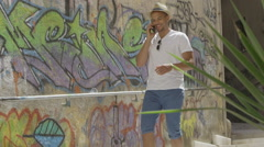 Attractive man with cell phone in European town with graffiti wall Stock Footage