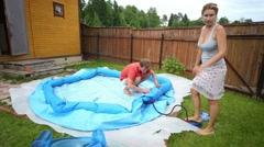 Man and woman is pumped large inflatable pool for children Stock Footage