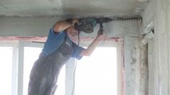 Young man in workwear makes hole in wall by large perforator Stock Footage