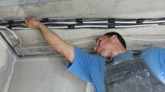 Bottom view of worker setting wires on ceiling for in apartment Stock Footage