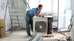 Worker sets air conditioner in apartment and talking on phone Stock Footage