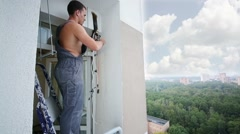 Worker on ladder sets fasteners for split system air conditioner Stock Footage