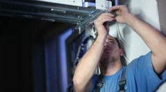Young serious worker sets split system air conditioner outdoor Stock Footage