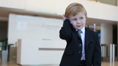 Little cute boy in business suit and tie talks on phone Stock Footage