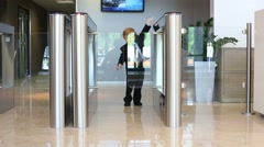 Little boy in suit goes glass turnstile in business center Stock Footage
