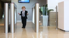 Little cute boy in suit goes glass turnstile in business center Stock Footage