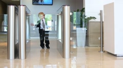 Little happy boy in suit with tie goes glass turnstile Stock Footage