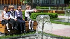 Four children in business clothes sit on bench near fountain Stock Footage